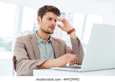 Pensive young businessman working with laptop indoors