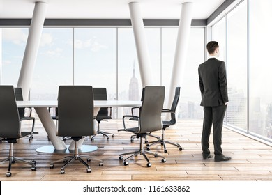 Pensive young businessmen standing in modern meeting room interior with panoramic city view. Career, job and occupation concept.