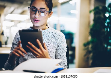 Pensive young businesswoman  reading information doing money transaction via tablet banking application, female student watching tutorial on touchpad online doing homework task in coworking space