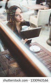 Pensive young businesswoman using tablet computer in coffee shop