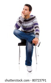 Pensive young casual man on a chair, isolated on white