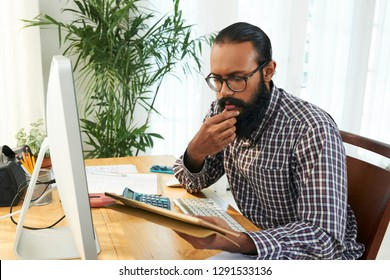 Pensive young casual programmer looking through online data in gadget and trying to decode it