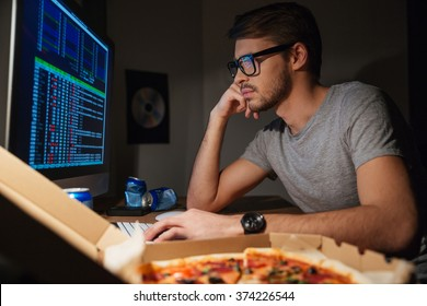 Pensive young developer in glasses using computer and coding at home