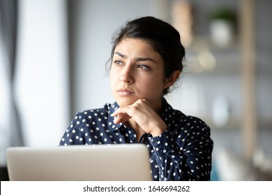Pensive young ethnic woman distracted from computer work look in window distance thinking, thoughtful millennial Indian girl lost in thoughts pondering solving problem, making decision