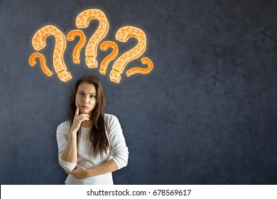 Pensive young european woman standing on concrete wall background with drawn question marks and copy space