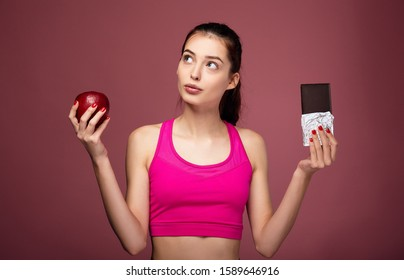 Pensive young girl athlete in a pink sports top holds a red apple and chocolate in her hands. Cute fitness lady holds a red apple and chocolate in her hand and makes a choice on a pink background.