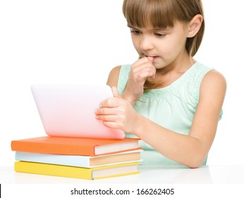 Pensive young girl is using tablet while studying, isolated over white