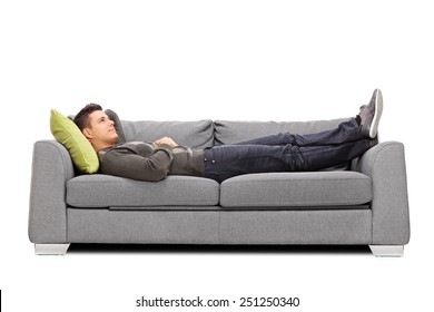 Pensive young guy laying on a sofa isolated on white background