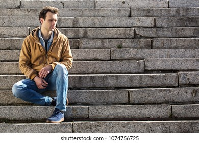 Pensive young guy sits on the steps