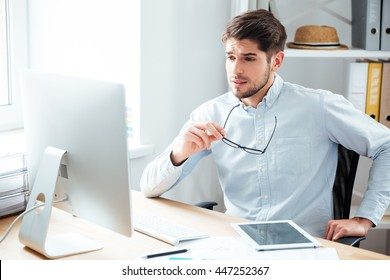 Pensive young handsome businessman holding eyeglasses and looking at computer monitor