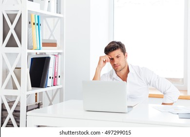 Pensive young handsome businessman looking at computer monitor sitting at the office