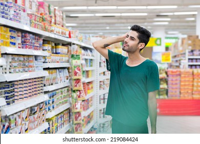 Pensive young man choosing food in the supermarket