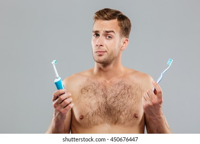 Pensive young man choosing toothbrush isolated on the gray background