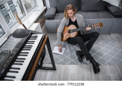 Pensive young man is composing song at home. She is writing words into the notebook with inspiration while sitting on floor and holding guitar