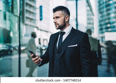 Pensive young man in elegant wear thoughtful looking away and thinking on content from received cell email, Caucasian intelligent trader waiting for personal lawyer in downtown holding smartphone