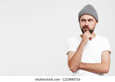 Pensive young man in grey hat, raised hand to face, touches his beard, looks dissatisfied suspiciously with disbelief on the left on blank copy space, lips pursed, isolated over white background