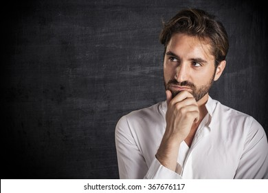 Pensive young man looks at copy space