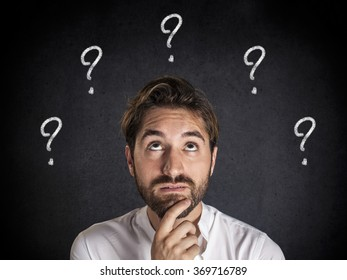 Pensive young man looks up at question marks