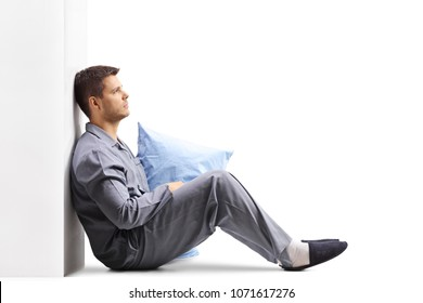 Pensive young man in pajamas holding a pillow and leaning against a wall isolated on white background