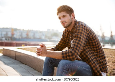 Pensive young man in plaid shirt sitting and thinking outdoors