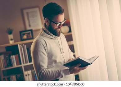 Pensive young man reading a book in his home library