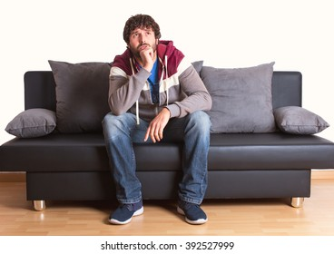 pensive young man sitting at home on sofa