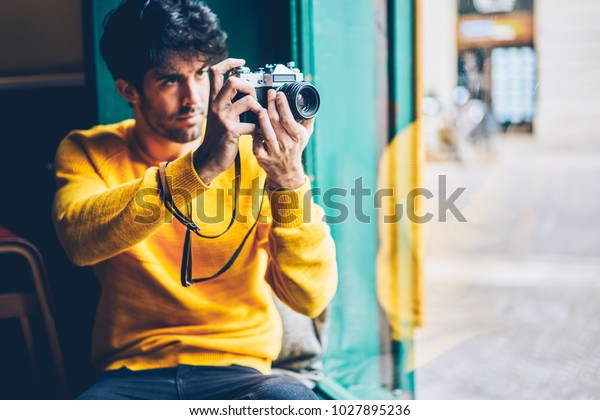 Pensive young professional photographer choosing filters on display and making photos on vintage camera.Concentrated bearded man spending leisure time in coworking to taking pictures out of window