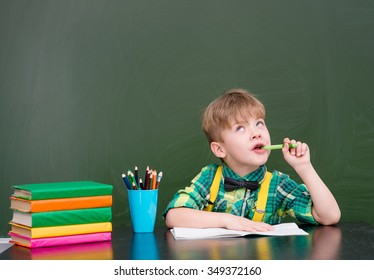 Pensive young student near empty green chalkboard