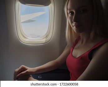 Pensive young woman in a airplane.