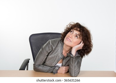 A pensive young woman at the desk, isolated on white