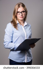 Pensive young woman in glasses and a light shirt standing and holding clipboard and pen over grau background