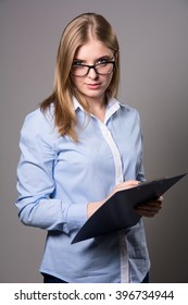 Pensive young woman in glasses standing and holding clipboard and pen over grau background