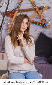 Pensive young woman with hand on chin looking at camera