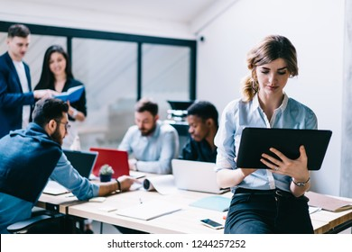 Pensive young woman searching information on internet websites on digital touch pad device while team of diverse colleagues collaborating on common project on background in modern office interior