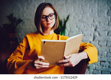 Pensive young woman with short haircut reading literature book resting in coffee shop interior in free time.Concentrated smart student enjoying bestseller sitting in coworking space