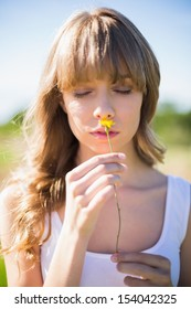Pensive young woman smelling flower while having a walk on sunny day