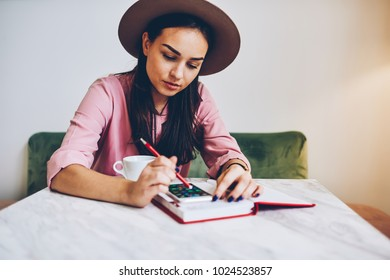 Pensive young woman in trendy hat installing application on smartphone for organizing day sitting in cafe,female student texting message on mobile phone chatting in social network during break