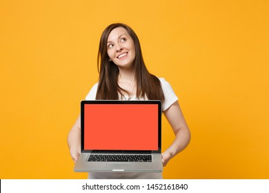 Pensive young woman in white casual clothes holding laptop pc computer with blank empty screen isolated on bright yellow orange wall background in studio. People lifestyle concept. Mock up copy space