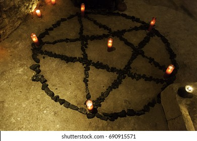 Pentacle satanic with candles in a dark ritual, detail of black magic and beliefs