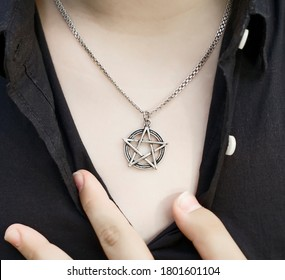 pentagram pendant on the chest of a woman. ring on male finger. close up image. In Freemasonry, the five-pointed star symbolizes light, knowledge and perfection.