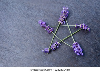 Pentagram - Witch, Wicca, Pagan symbol made of purple lavender flower spikes against gray / grey slate background