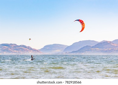 PENTICTON, BRITISH COLUMBIA, CANADA - OCTOBER 24, 2017: a man kitesurfing on Skaha Lake by Sudbury Beach on a sunny autumn day. Skaha Lake is a popular location for this sport.