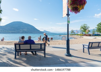 Penticton, British Columbia/Canada - June 22, 2019: people sit on benches, walk along Lakeshore Drive and enjoy the beach on Okanagan Lake during the summer tourist season.