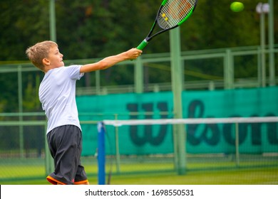 Penza Russia 0 7 .0 9 .2019 .a boy in a gray t shirt and black shorts plays tennis on a grass court