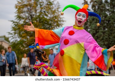 Penza Russia. 06. 09 2019  a buffoon in a headdress with bells brightly colored clothes speaks on the streets