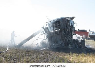 PENZANCE, SASKATCHEWAN - AUGUST 27, 2017.  Volunteer firemen extinguish a burning combine during harvest