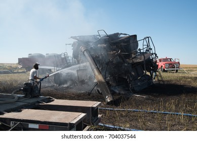 PENZANCE SASKATCHEWAN - AUGUST 27, 2017.  Volunteer firemen extinguish a burning combine during harvest