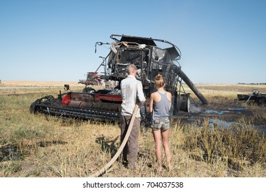 PENZANCE, SASKATCHEWAN, CANADA - AUGUST 27, 2017. A young couple survey the ruins of a combine that caught fire in a field during harvest after the fire is extinguished