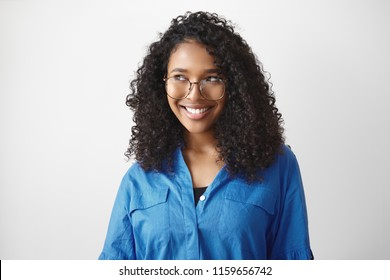 Peolple, style, fashion, eyewear, optics and vision concept. Cute beautiful young African American woman with curly hair smiling broadly, feeling happy because she able to see clearly using eyeglasses