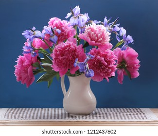 Peonies and irises. Beautiful bouquet of garden flowers in a jug on a blue background.